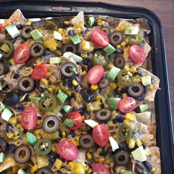 These loaded sheet pan chicken nachos have it all, from the flavorful salsa chicken, to the crunchy peppers & corn, to the hearty black beans. Try loaded baked chicken nachos the next time you have some leftover chicken -- for a fun dinner change of pace, or hearty movie night appetizer!
