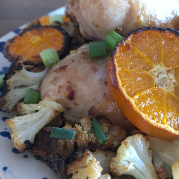 plate of chicken drumsticks with clementines and cauliflower