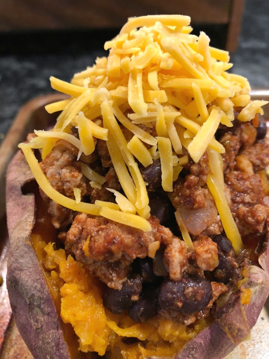 These flavorful turkey taco stuffed sweet potatoes are super easy to make, and naturally gluten free. Give this easy turkey tacos recipe a try on your next Taco Tuesday! Top the turkey taco sweet potatoes with a little shredded cheese + your own favorite taco toppings.