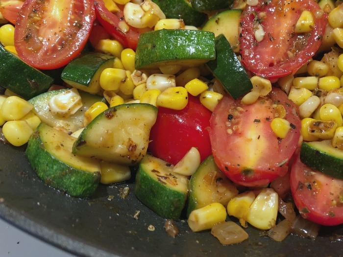 corn, zucchini, tomatoes in skillet