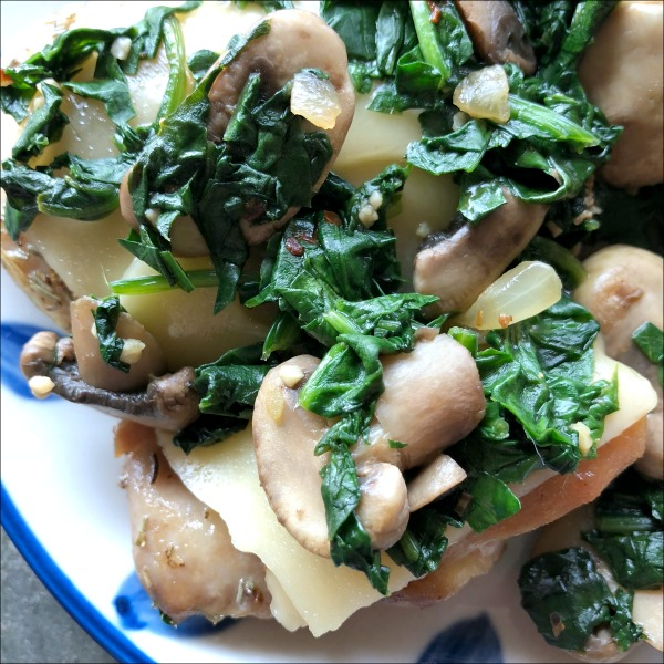 chicken topped with cheese, spinach, and mushrooms