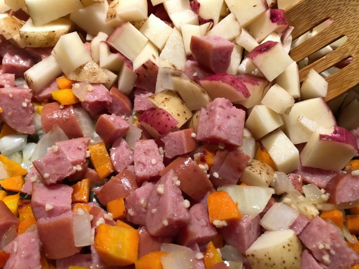 sausage, carrots, onions, and potatoes in a pot