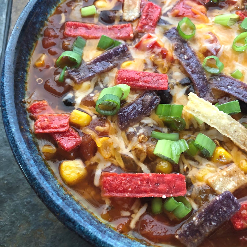 vegetarian taco soup in a bowl topped with cheese, green onions, and tortilla strips
