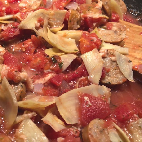 adding artichokes and tomatoes to chicken sausage in a pan