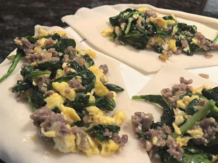 adding filling to sausage, egg, & spinach hand pies