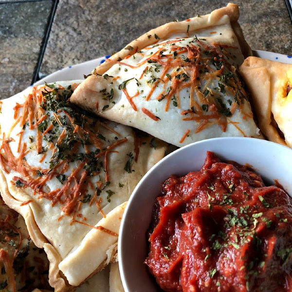 pepperoni pizza pockets on a plate with sauce