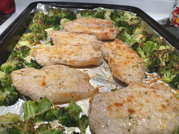 Finished pork chops and broccoli on a baking sheet