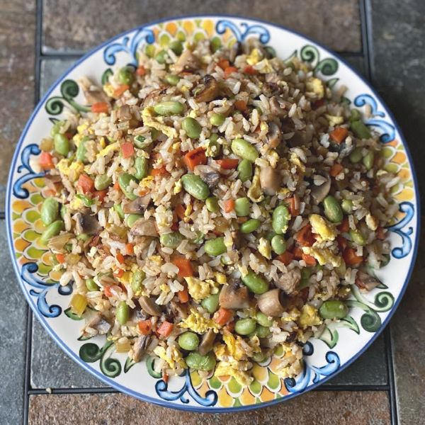 Plate of vegetable fried rice with edamame, mushrooms, carrots...