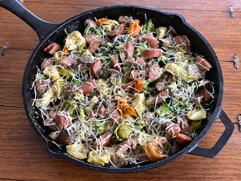 Skillet full of tortellini sausage and veggies with Parmesan on top