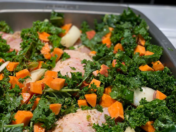 Arrange the kale and the sweet potatoes around the chicken in the pan