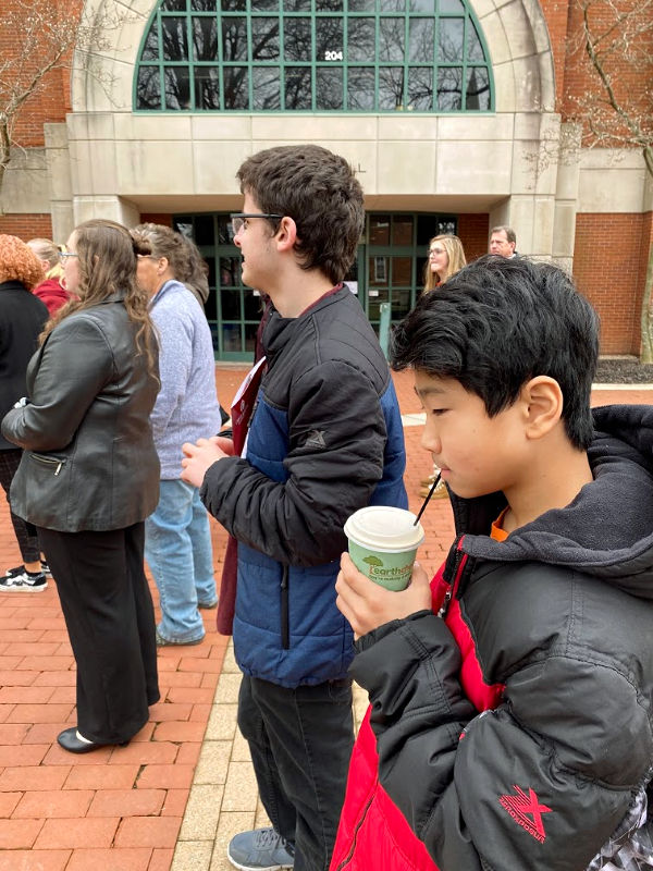middle school kid drinking coffee on a college tour
