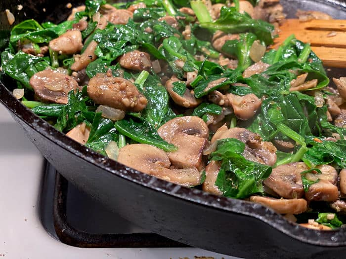 cooked spinach & mushrooms in a cast iron skillet