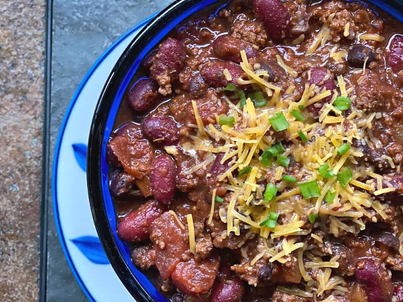 bowl of chili with cheese and green onion