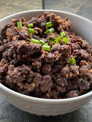 Bowl of slightly smashed garlicky baked beans -- a side dish or burrito filling