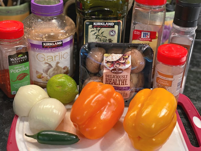 veggie fajitas ingredients -- peppers, onion, mushrooms, garlic, spices, lime juice