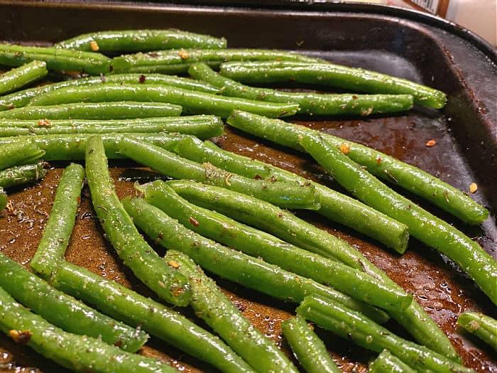 season the green beans on baking sheet