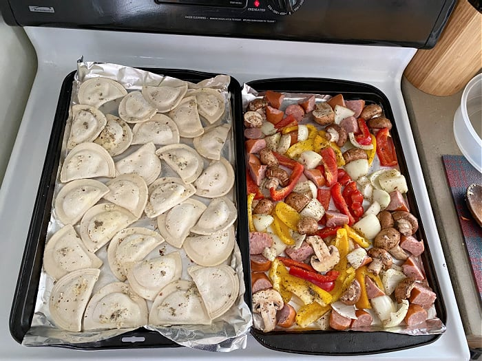 baking sheets of sausage and pierogies