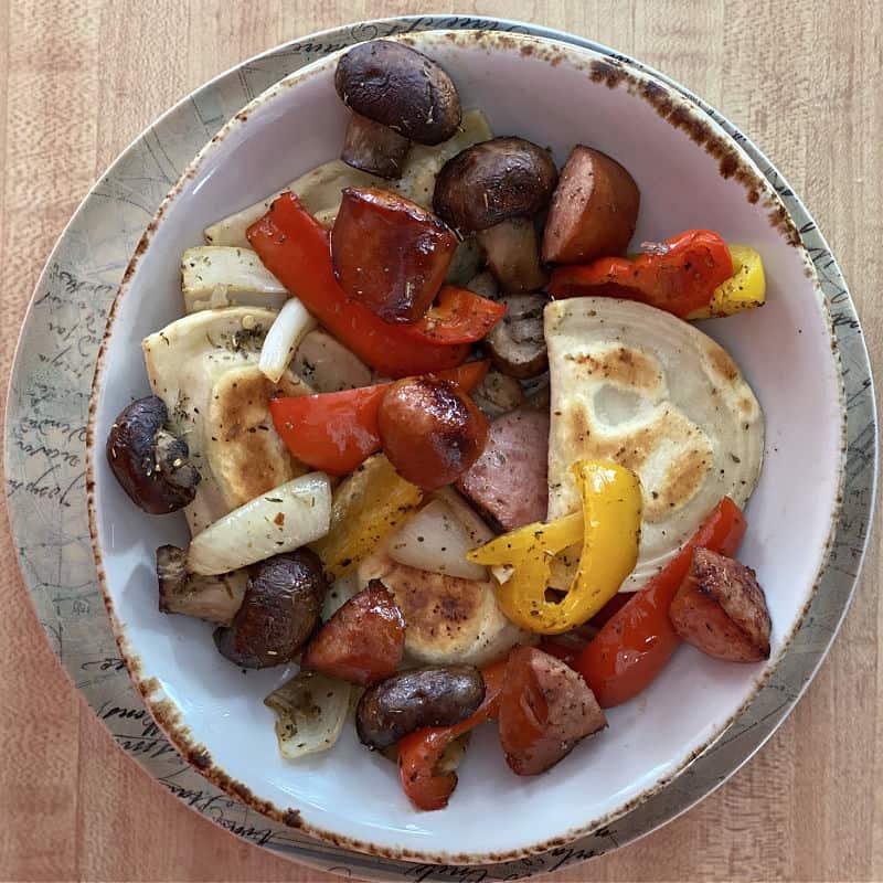 Bowl of sheet pan sausage peppers and pierogies