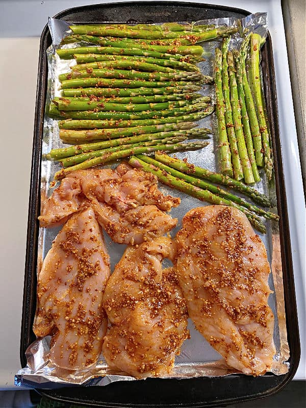 chicken and asparagus on a baking sheet