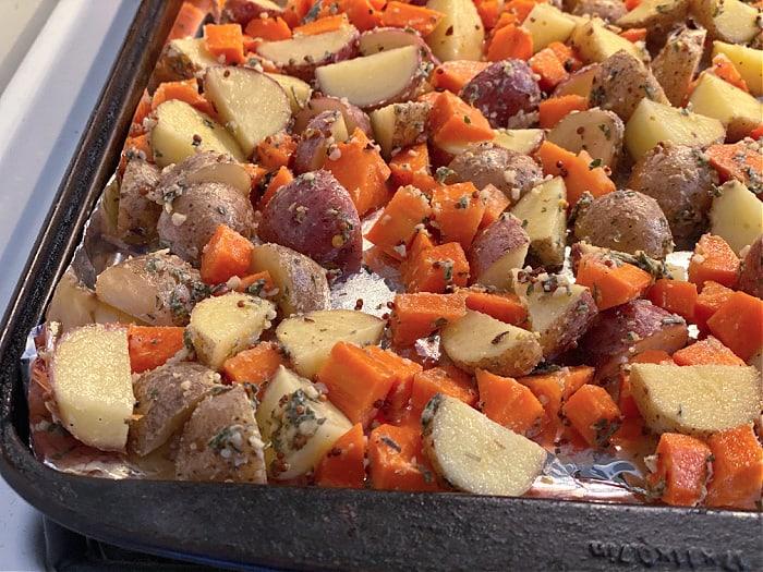 seasoned potatoes and carrots on a sheet pan