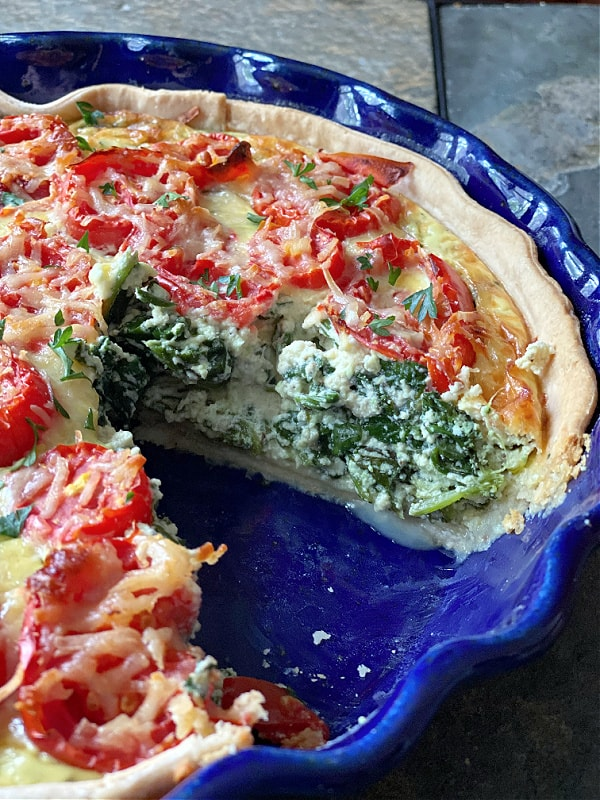 spinach, ricotta, and tomato quiche with a slice cut out