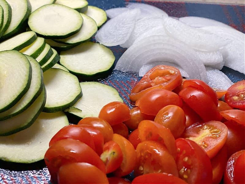 slice up tomatoes zucchini and onion